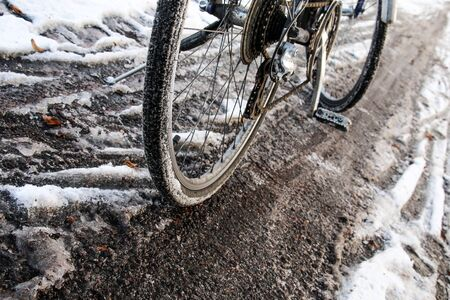 A detail of the bicycle on the dirty cycleway during winter. Only narrow track is visible and can be used.