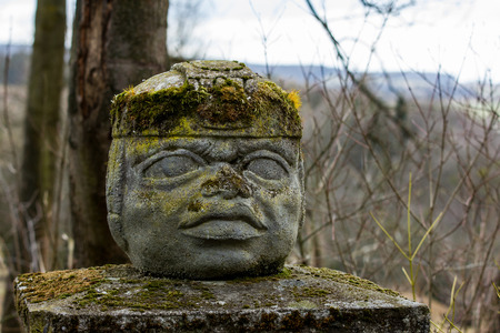 The Aztec statue on a pylon. The head or face is made from stone and covered with moss.