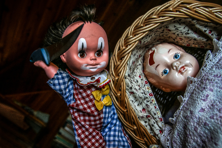 The unused old doll with a hole in its head is lying in the baby carriage and looking quite scary and depressive. The second doll is holding the knife above it. Looks like doll murder.