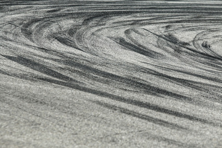 The rubber tracks from the rallye cars left on the tarmac in the hairpin. Stock Photo - 121472763