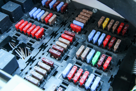 The detail of the fuse box in the car´s engine room. Many fuses with different values of current.
