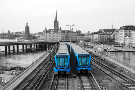 A traditional modern swedish metro train in Stockholm is driving on the bridge from the old town centrum.