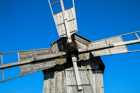 Detail of an old wooden windmill. You can see the upper part of it.