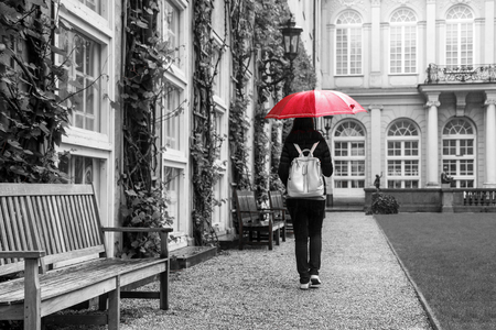 The woman with the red umbrella is walking in the historical garden of a castle during the rainy day.