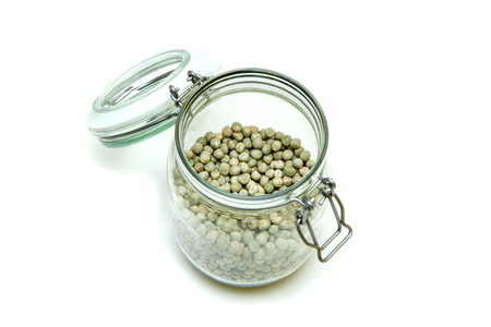 The green peas stored inside the closable glass bottle isolated on a white background.