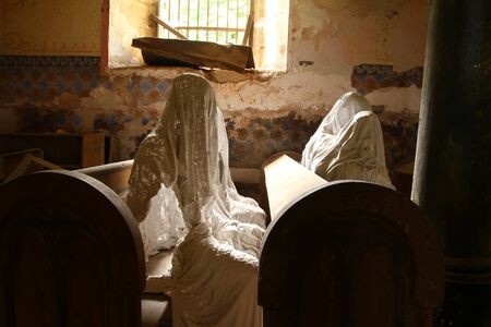 The picture from the interior of the old abandoned, almost destroyed church in Czech Republic. Inside are the statues of believers ghosts. Banco de Imagens