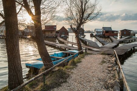 """A picture taken by the Bokod lake in Hungary during the evening. The """"floating"""" houses on pillars can be seen. The sun is going down behind the haze. A nice, calm and lonely place."""