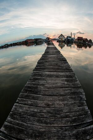 """A picture taken by the Bokod lake in Hungary during the evening. The """"floating"""" houses on pillars can be seen. The sun is going down behind the haze. A nice, calm and lonely place. Stock fotó"""