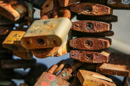 A detail of several old and rusty locks hanging on a handrail on a bridge.
