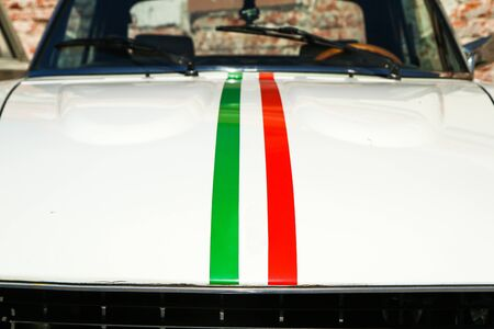 The detail of a bonnet of and old Italian sports car. The sticker stripe it in Italian colors according to the flag.