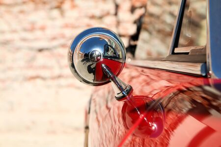 The detail of a side mirror of the old Italian sports car.