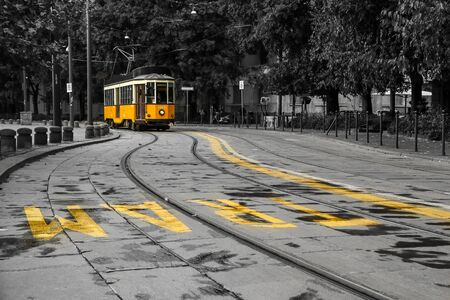 A picture of the typical yellow tram in Milan, Italy, passing throught the city center. The tram is isolated in the black and white background.