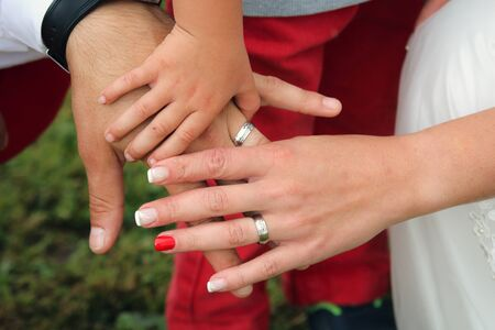 The detail of the hands of the bride and groom during the wedding ceremony. They are together with their child. It symbolises the family and parenthoo