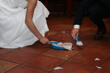 A traditional wedding custom for the newly married couple. The plate is thrown on the floor and broken. They have to clean the mess. The shards will bring the happiness for them.