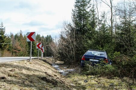 A car destroyed during the traffic accident. The car is abandoned and stands by the road in the trees. Stock Photo