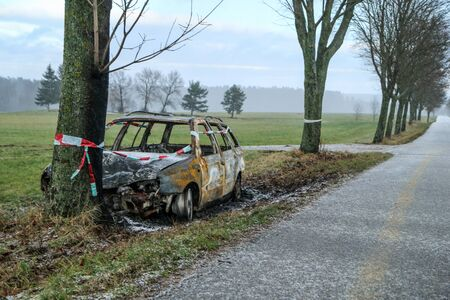 Car destroyed during the traffic accident. It was caused by the bad weather conditions in winter, because of the black ice or snow. The car is burnt, abandoned and stands by the road in the snowfall.