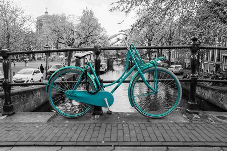 Ein Bild eines einsamen azurblauen Fahrrads auf der Brücke über den Kanal in Amsterdam. Der Hintergrund ist schwarz-weiß.