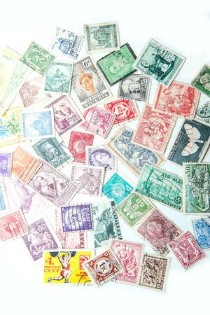 An assorted mixture of the old european and world stamps is lying on the table. Stamps are colorful and various. Stok Fotoğraf