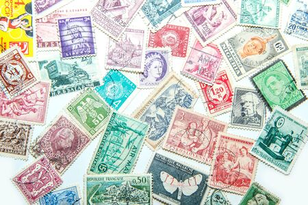 An assorted mixture of the old european and world stamps is lying on the table. Stamps are colorful and various. Imagens