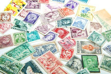 Un mélange assorti d'anciens timbres européens et mondiaux est posé sur la table. Les timbres sont colorés et variés. Banque d'images