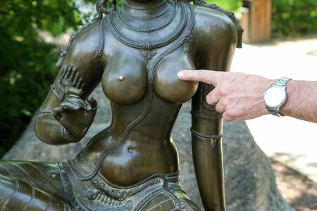 The detail of man´s hand touching the nipple of the bronze woman statue. Standard-Bild