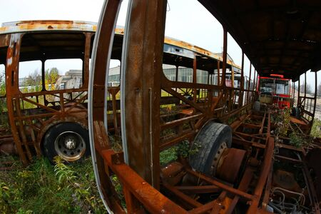The wrecks of the buses standing on the vehicle cemetery. Waiting to be scrapped. Only rusty constructions sometimes remain.