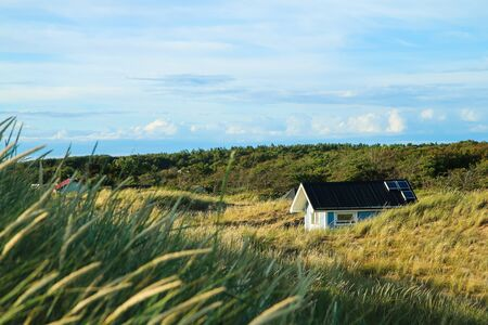 The traditional colorful wooden recreational cottages by the coast of the sea in Sweden, hidden behind the dunes. Stock fotó - 138182648