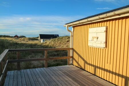 The traditional colorful wooden recreational cottages by the coast of the sea in Sweden, hidden behind the dunes. Stock fotó