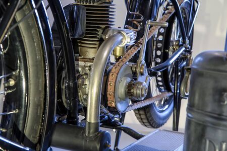 The detail of the old motorcycle with part of the frame, engine, fuel tank and leather belt for power transmission.