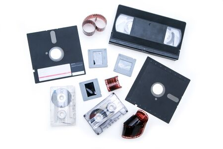 A group of old retro audio visual equipment used to capture or record  pictures, video, audio or data. The floppy disc, audio and video cassettes, fil
