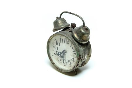 The old retro alarm clock with bit of rust and patina isolated in a white background.