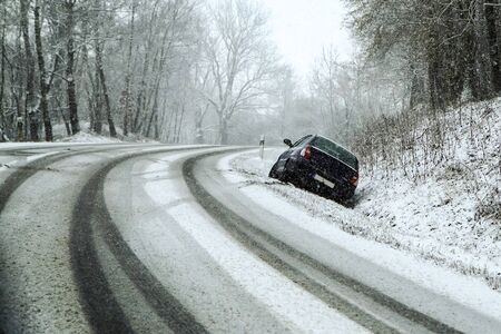 Abandoned car in the ditch after the traffic accident. Symbolises the dangerous conditions in winter with ice, snow and snatch.