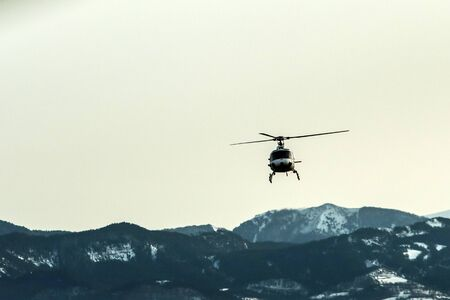 An atmospheric picture shows the helicopter climbing in front of the high snowy mountains. Reklamní fotografie