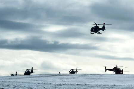 An atmospheric picture shows the helicopter landing on the snowy field. Other helicopters are standing on the ground. Reklamní fotografie
