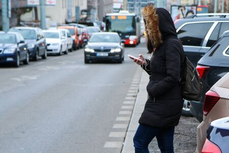 Illustration of the problem of the modern age. Called digital zombie. People are watching their smart phone with hood and headphones and don´t pay attention Reklamní fotografie