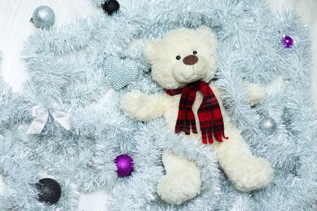 A cute teddy bear is lying in the christmas decoration and relaxing.