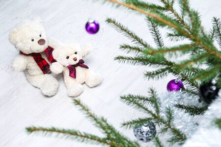 Two cute teddy bears are sitting by the christmas tree and watching, how beautiful it is.