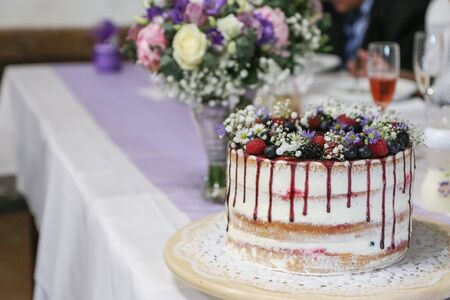 A detail picture of the big wedding cake with forest fruits and strawberries.