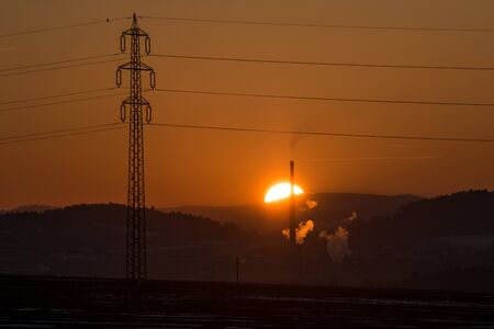 A sunset behind the heating plant. The plant releases steam. In front, the transmission tower stands.