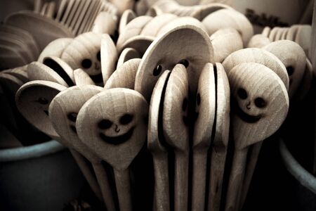 A detail picture of the wooden cooking spoons with carved faces. They are smiling, but also look a bit scary, like some ghosts. Reklamní fotografie