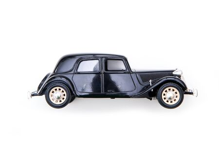 The black toy model of the old retro car. Isolated on a white background.
