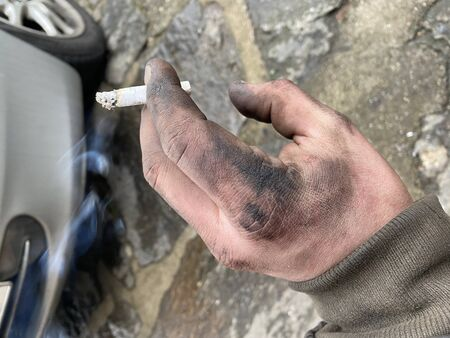 A picture of dirty hand of a guy from the garage. Hard and dirty work is behind him. Having a rest with the ciguarette