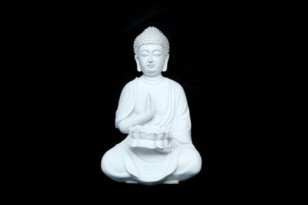 The white statue of the calm sitting buddha isolated in a black background. Standard-Bild