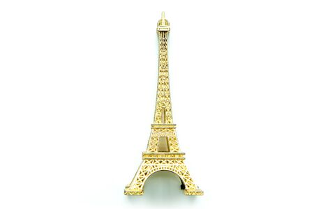 The small golden Eiffel tower as a souvenir from Paris. Isolated on a white background.