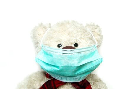 The plush teddy with a mask on his face. as a symbol of protection against viruses like corona virus. Everybody has to wear a mask.