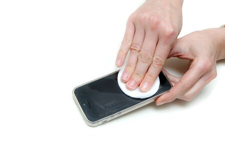 The detail of hands cleaning the mobile phone´s display with a tampon with a disinfection. Protection agains transfer of the viruses and diseases.