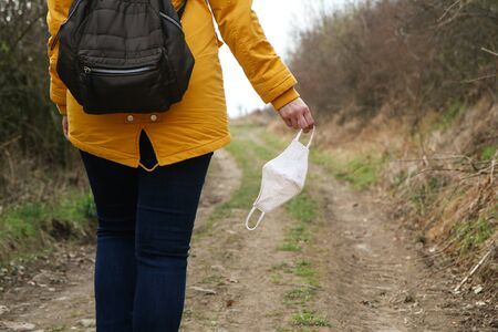Woman is holding a textile face mask used for protection against viruses while walking in the nature. Symbol for protest against regulations or freedom after the end of quarantine.
