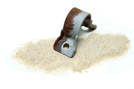 The overgrown rusty cast iron part partly sand blasted together with sand isolated in a white background.