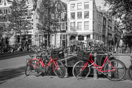A picture of two red bikes on the bridge over the channel in Amsterdam. The background is black and white.