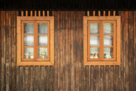 A detail of the planks on the facade of the  wooden house with a window. The color of the house is old and looks shabby. Imagens